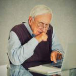 confused-grandfather-using-pc-computer-sitting-desk-50353800